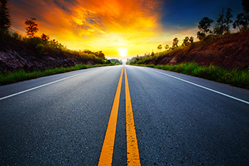 Asphalt road with greenery on sides facing the sunset representing Financial Planning